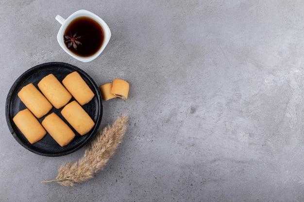 Schwarzer teller mit süßen keksen und tasse tee auf steintisch.