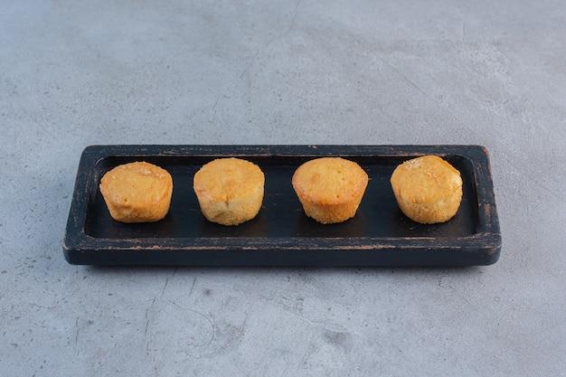 Schwarzer teller mit süßen minikuchen auf stein.