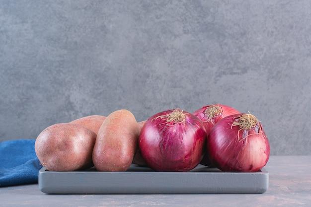 Schwarzer teller mit süßkartoffeln und roten zwiebeln auf steinoberfläche