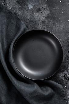 Schwarzer teller und ein handtuch auf strukturiertem schwarzem hintergrund