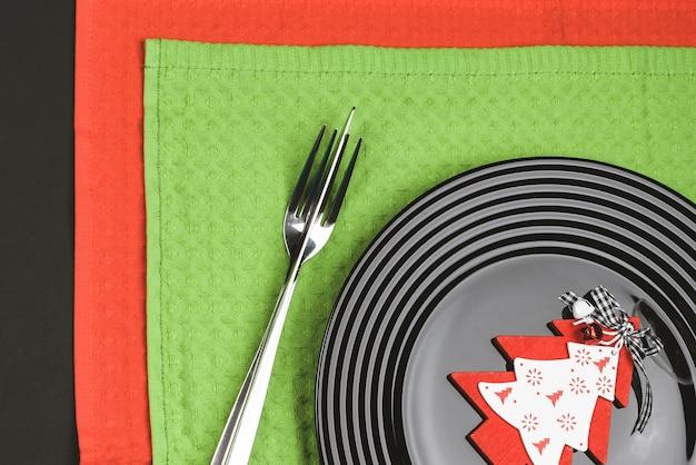 Schwarzer teller und weihnachtsdekoration für feiertagsmenü