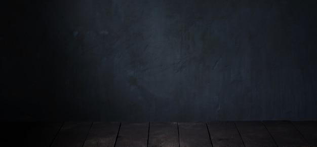 Schwarzer tisch auf dunkler hintergrundwand