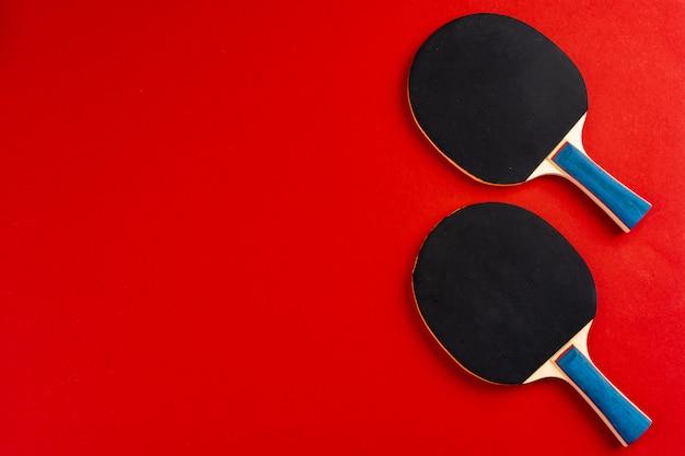 Schwarzer tischtennisschläger auf rotem hintergrund