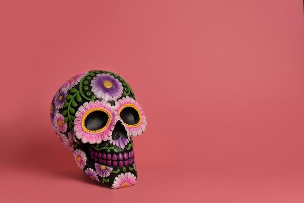 Schwarzer totenkopf ist mit lila und rosa blüten verziert