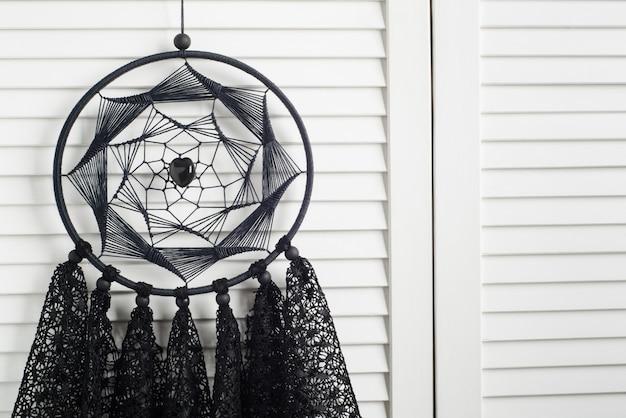 Schwarzer traumfänger mit gehäkelten deckchen