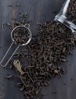 Schwarzer trockener tee in sieb, glas, schaufel auf einer holzoberfläche flach liegen.