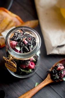 Schwarzer trockener tee mit blattminze und trockener himbeere im glas und holzlöffel auf dunklem holztisch, obstsnack, honig und pastille gemütliche teezeit. natürliches licht, selektiver fokus