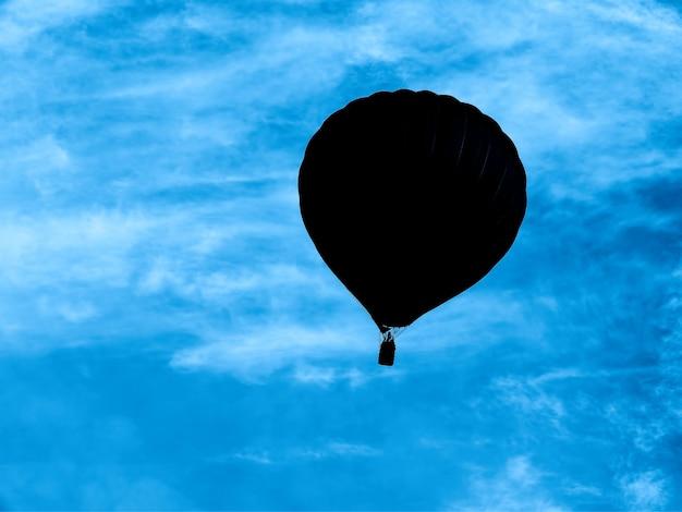 Schwarzer umriss des ballons im hintergrund des blauen himmels