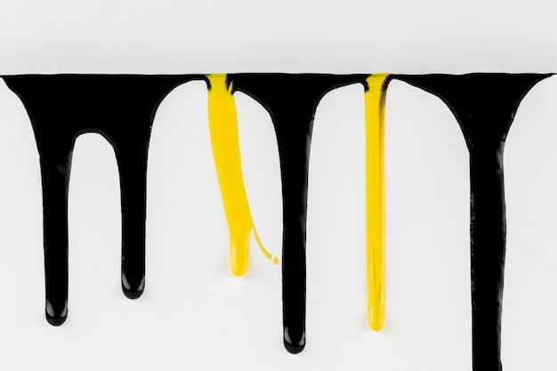 Schwarzer und gelber lack, der auf weißem hintergrund tropft