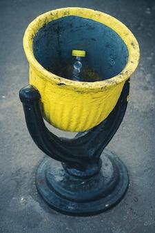Schwarzer und gelber stahlmülleimer auf der straße