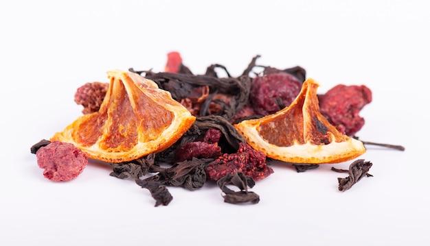 Schwarzer und grüner chinesischer tee mit erdbeeren, kirschen und orange lokalisiert auf einem weißen hintergrund.