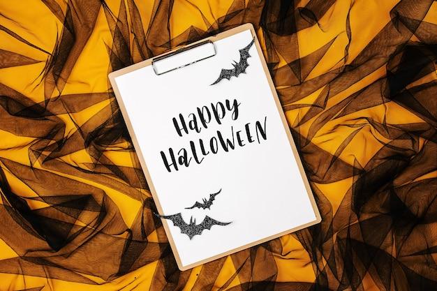 Schwarzer und oranger abstrakter hintergrund mit zwischenablage und fledermäusen, konzept für halloween
