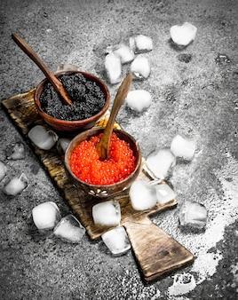 Schwarzer und roter kaviar in einer schüssel auf dem alten brett. auf rustikalem hintergrund.