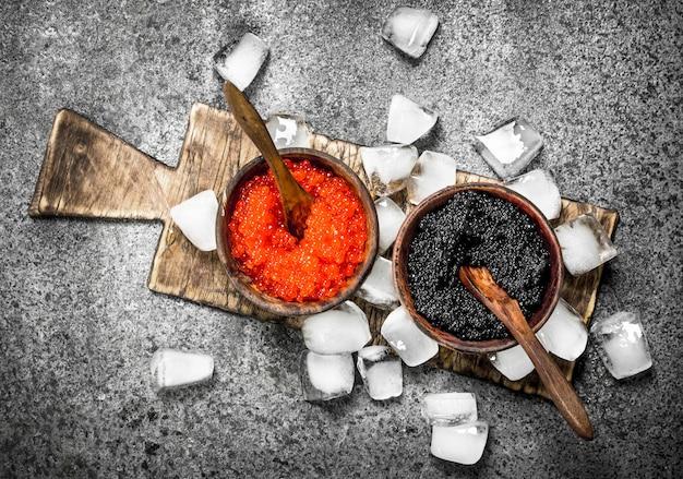Schwarzer und roter kaviar in einer schüssel auf dem alten brett.