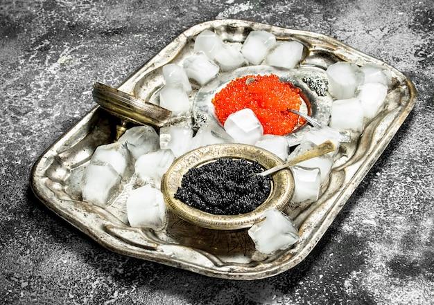 Schwarzer und roter kaviar in schalen auf altem tablett.
