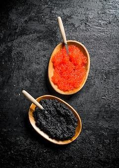 Schwarzer und roter kaviar in schalen mit löffeln. auf schwarzem rustikalem hintergrund