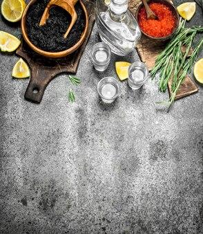 Schwarzer und roter kaviar mit einer karaffe wodka.