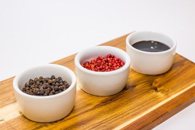 Schwarzer und roter pfeffer der nahaufnahme, soja auf holztisch. würz- und speziesbestandteilkonzept. zusammensetzung der kulinarischen zutaten. gewürze in weißen töpfen angeordnet.