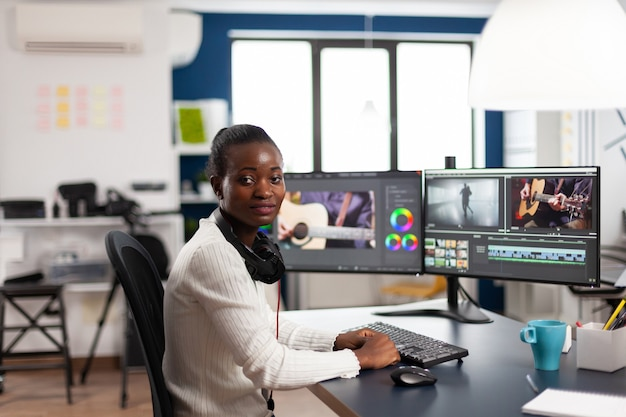 Schwarzer videofilmer, der an der kamera lächelt, die videoprojekt in der postproduktionssoftware bearbeitet, die im kreativstudiobüro arbeitet