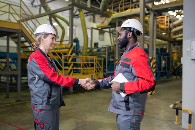 Schwarzer vorarbeiter mit tablette händeschütteln der arbeiterin beim einstellen in der fabrik