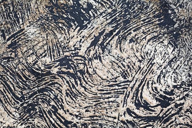 Schwarzer vulkansand vom strand auf der unebenen betonbodenoberfläche mit rauen gewellten pinselstrichen