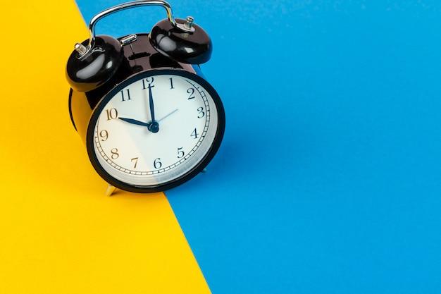 Schwarzer wecker auf dem farbblock gelb und blau