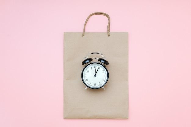 Schwarzer wecker auf handwerkspaket auf einem rosa hintergrund. konzept schwarzer freitag, saisonverkaufszeit