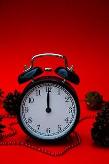 Schwarzer wecker auf rotem hintergrund mit weihnachtsschmuck und zapfen weihnachtshintergrund