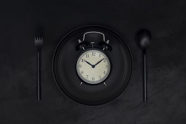 Schwarzer wecker auf schwarzem teller mit löffel und gabel auf schwarzem hintergrund. schwarzes monochromes konzept.