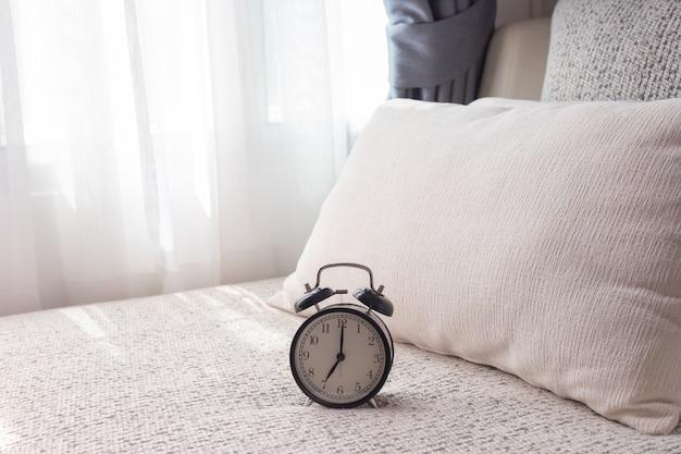 Schwarzer wecker auf weißem bett im wohnzimmer.