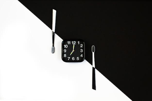 Schwarzer wecker mit manuellem zahnbürstensatz