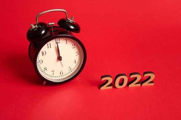 Schwarzer wecker mit mitternacht auf dem zifferblatt und holzzahlen als symbol für das jahr 2022. weihnachts- und neujahrsfeierkonzept lokalisiert über rotem farbigem hintergrund mit kopienraum für anzeige