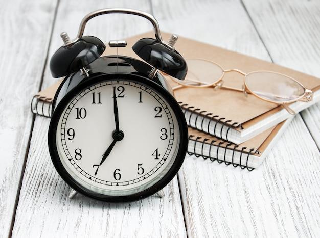 Schwarzer wecker, notizbücher und gläser