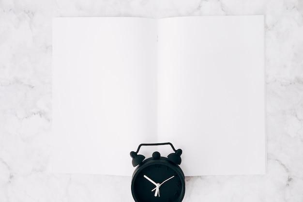 Schwarzer wecker über der weißen seite gegen marmor maserte hintergrund