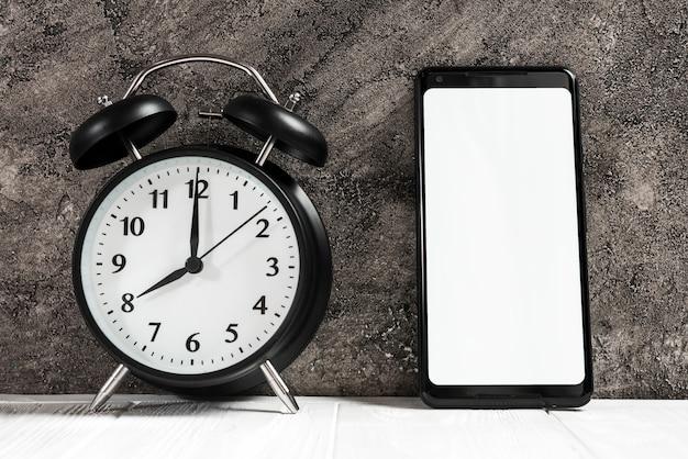 Schwarzer wecker und smartphone mit weißem leerem bildschirm auf schreibtisch gegen konkrete schwarze wand