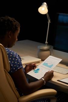 Schwarzer weiblicher fachmann, der am schreibtisch im büro nachts sitzt und geschäftsdiagramm betrachtet