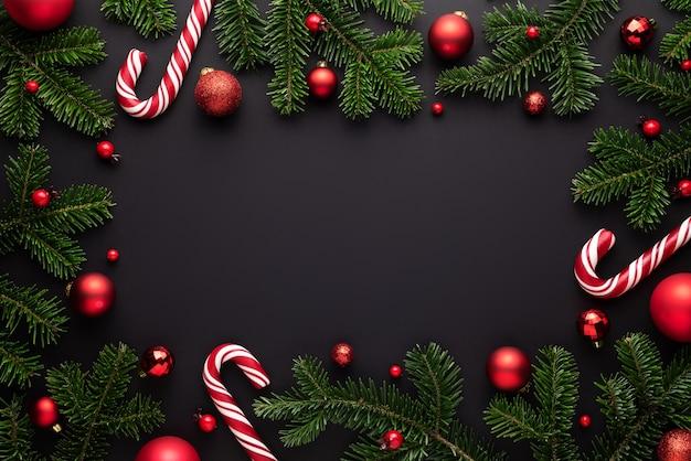 Schwarzer weihnachtshintergrund. dekorativer rahmen aus tannenzweigen, weihnachtskugeln und zuckerstangen