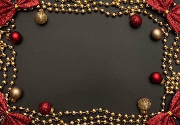 Schwarzer weihnachtshintergrund mit goldenen perlen, roten und goldenen weihnachtsdekorationen und roten schleifen. flacher laienstil. neujahrsgrußkarte.