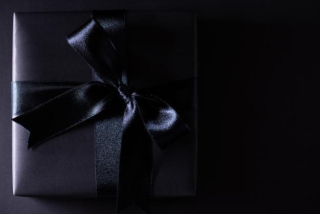 Schwarzer weihnachtskasten auf schwarzem mit copyspace, black friday.