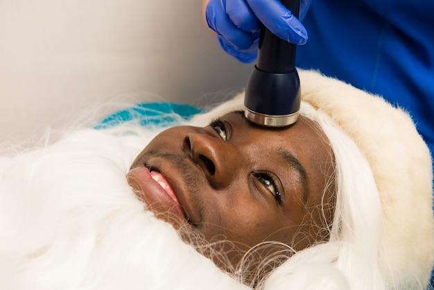 Schwarzer weihnachtsmann, der kosmetische eingriffe in der spa-klinik tut. kosmetische eingriffe in der spa-klinik. nahansicht