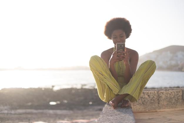 Schwarzes afrikanisches rennen junges schönes modellmädchen 25 jahre alt benutzt das telefon und überprüft die sozialen medien im internet, die an einer wand in der nähe des ozeans und des wassers mit hellem sonnenuntergang sitzen. fröhliche freizeitmenschen