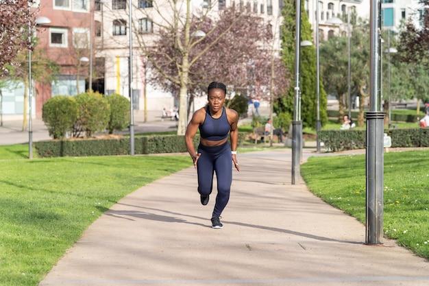 Schwarzes afro-mädchen, das in einem öffentlichen park als läufer verkleidet läuft
