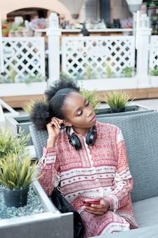 Schwarzes afro-mädchen im ethnischen kleid mit kopfhörern am hals, das im open-air-café sitzt, smartphone hält und an etwas denkt