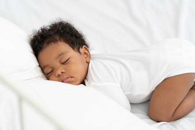 Schwarzes afroamerikanisches baby, das auf einer weißen matratze schläft.