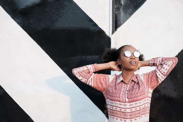 Schwarzes afroamerikanisches mädchen, das in der nähe des entkleideten riesigen tores steht und weit weg schaut.