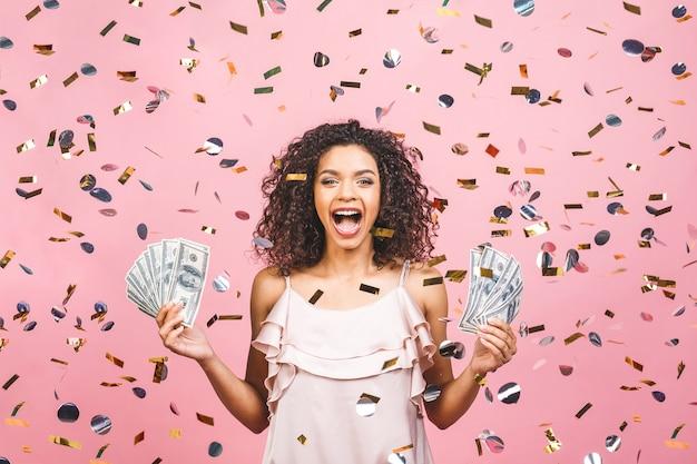 Schwarzes afroamerikanisches mädchen gewann geld. glückliche junge frau, die dollarwährung zufrieden hält, lokalisiert über rosa hintergrund mit konfetti.