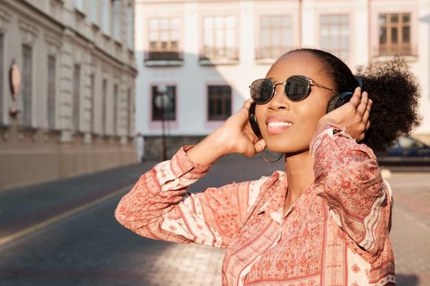 Schwarzes afroamerikanisches mädchen hat einen spaziergang in der abendstadt und hört musik in kopfhörern. mädchen in der sonnenbrille im sommer lächelt und schaut auf sonnenuntergang.