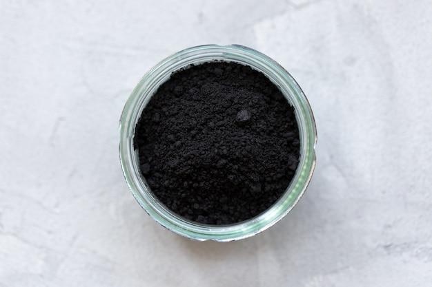 Schwarzes aktivkohlepulver in einem glas. superfood, zutat für kosmetik und veganes, vegetarisches essen, entgiftungskonzept. graue wand. kopierraum, selektiver fokus