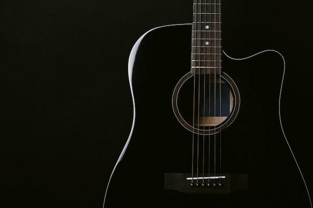Schwarzes akustisches gitarrenstudio schoss auf schwarzem hintergrund