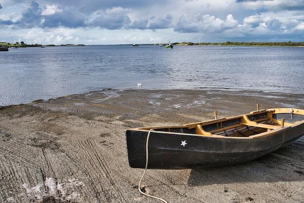 Schwarzes altes boot auf dem sand